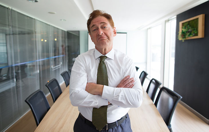 Skeptical senior businessman standing in boardroom