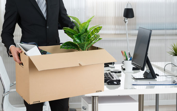 Man with box cleaning out desk